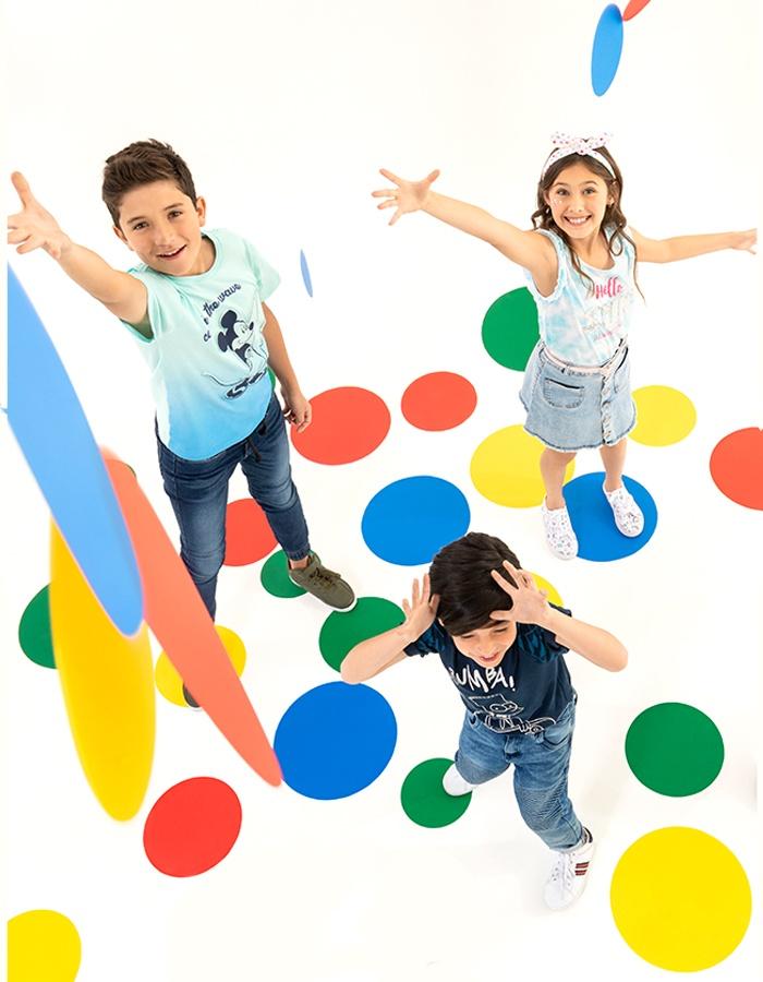 Un par de niños sonriendo y jugando twister, con pantalón de mezclilla.