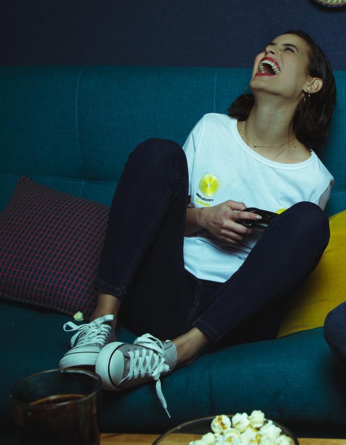 Una mujer con Jeans y Blusas sentada en un sillón